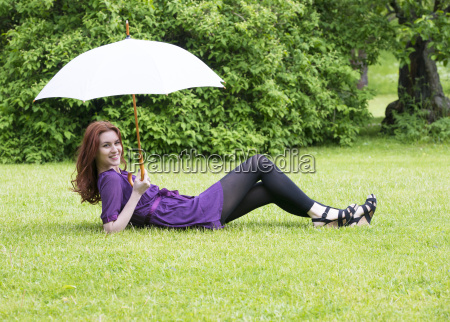 young woman with umbrella lying in