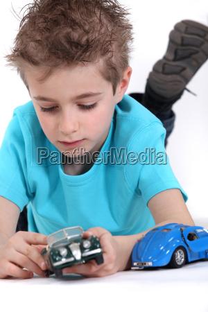 kleiner junge spielt mit spielzeugautos