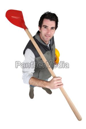 tradesman carrying a spade