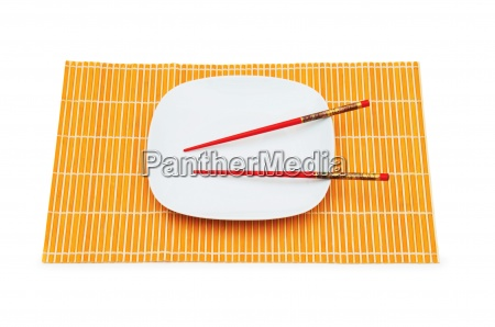plate with red chopsticks isolated on