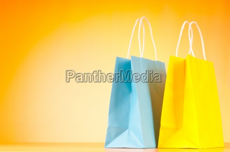 colourful paper shopping bags against gradient
