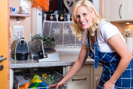 hausfrau beim geschirr abwaschen mit geschirrspueler