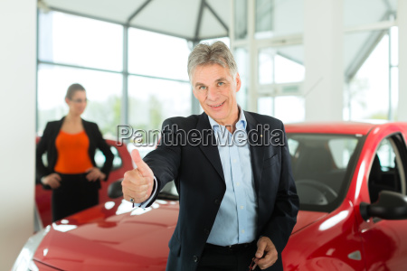 elderly man with car and woman
