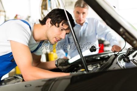 kunde und mechaniker an auto schauen