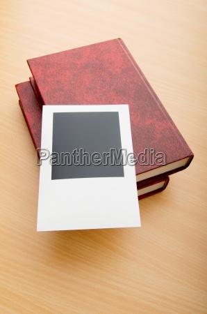 buecher und leere fotos auf holztisch