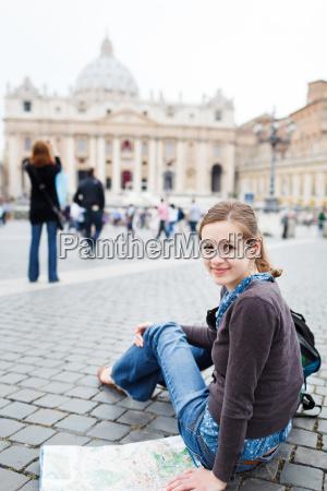 huebsche junge weibliche touristen eine karte