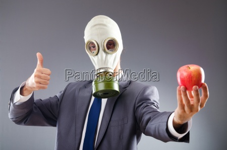 geschaeftsmann mit gasmaske und apfel