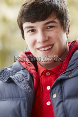 teenage boy wearing earphones and listening