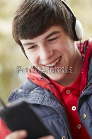 teenage boy wearing headphones and listening