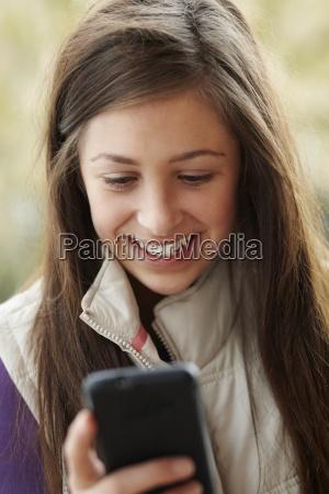 teenage girl texting on smartphone wearing
