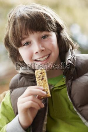 boy eating healthy snack bar wearing