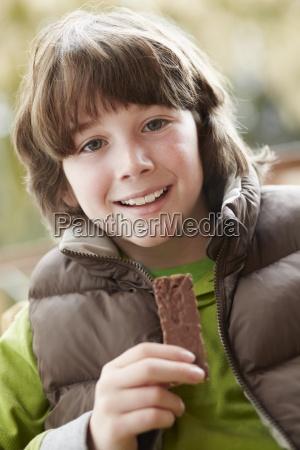 boy eating chocolate bar wearing winter