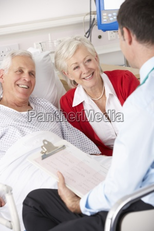 doctor talking to senior couple on