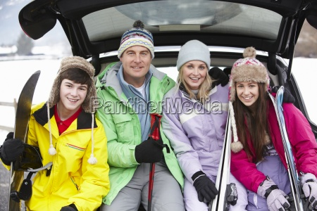 teenage family sitting in boot of