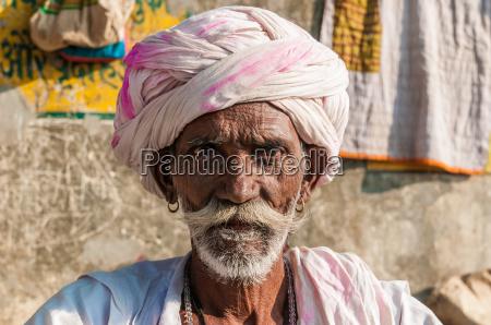 ein alter sitzender indischer mann mit