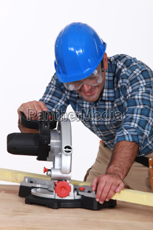 carpenter using saw mounted to work