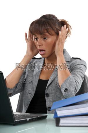alarmierte frau schaut auf ihren laptop