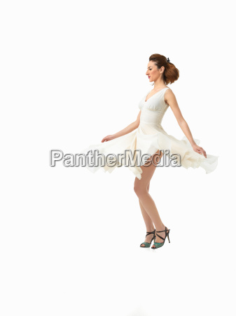 beautiful young woman twirling in white