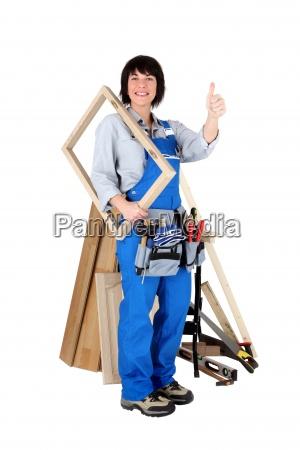 female carpenter holding wooden frame