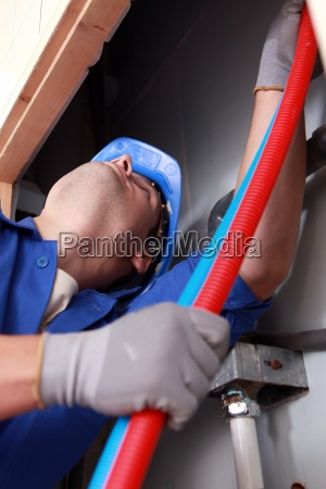 plumber installing plastic domestic water pipes