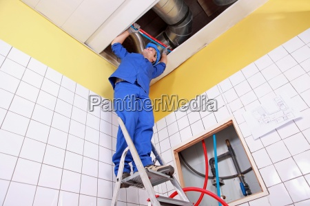 plumber working on a ladder