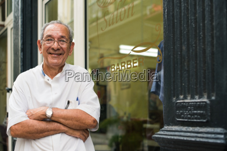 portrait of old barber smiling in