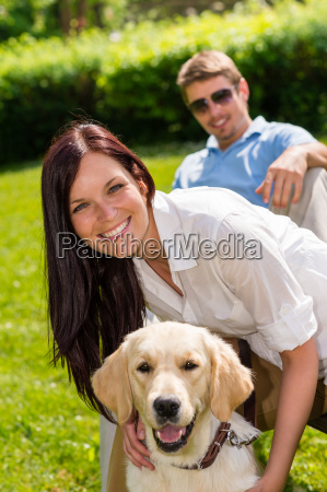 couple sitting with golden retriever in