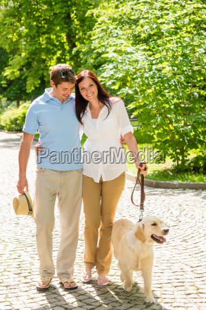 young couple in love walking dog