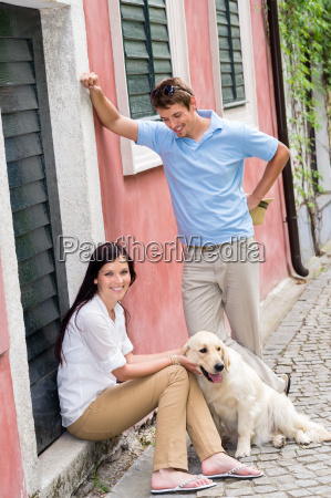 happy couple resting with dog on