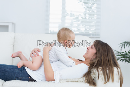 mother lying on a sofa holding