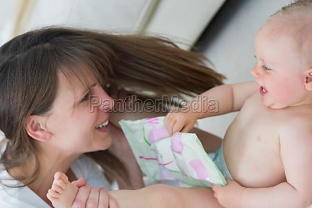 baby lying on back while holding