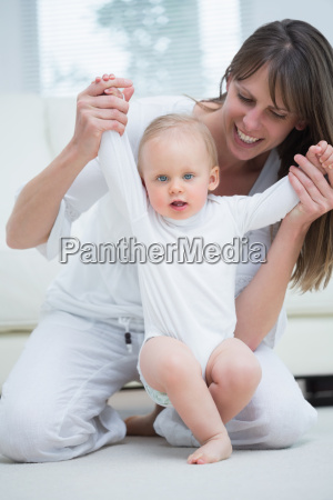 mother raising arms of her baby