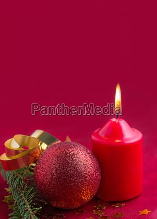 weihnachtsdekoration mit christbaumkugeln und kerze