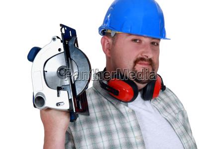 bearded man holding circular saw
