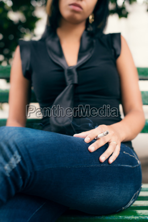 young woman smoking cigarette on bench