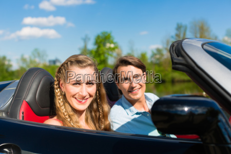 young couple with cabriolet in summer