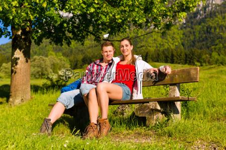 glueckliches paar sitzt auf bank vor