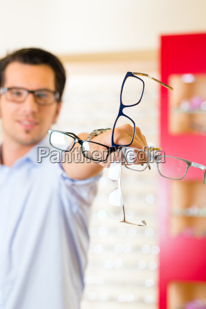 young man at the optician buying