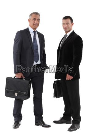 zwei geschaeftsleute mit aktenkoffer