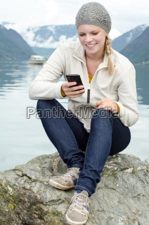 junge blonde frau mit ihrem smartphone