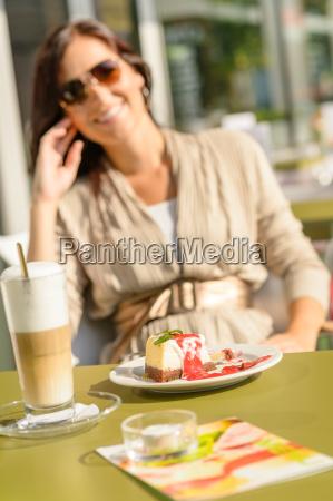 kaesekuchen und latte cafe terrasse frau