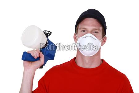 tradesman holding a spray gun and