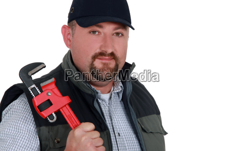 construction worker holding a pipe wrench