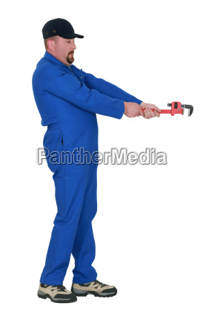 plumber with wrench pretending to loosen