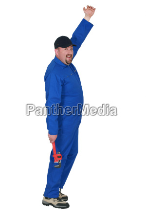 plumber in boiler suit holding wrench