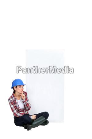 tradeswoman sitting cross legged by an
