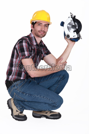 man crouching down whilst holding circular