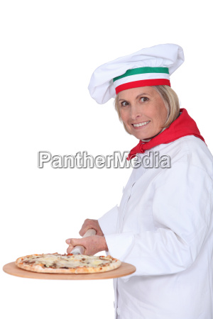 senior female cook preparing pizza