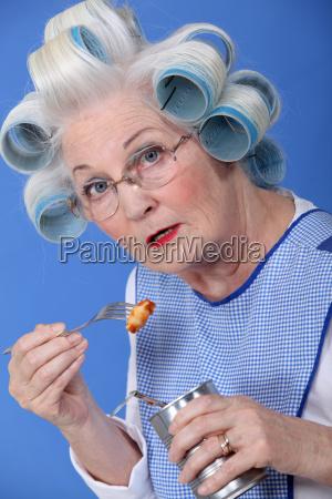 lustige grossmutter mit gabel konserven essen