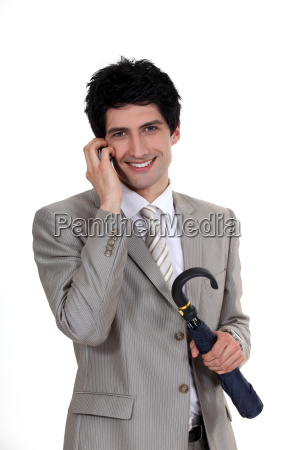 businessman holding an umbrella and talking